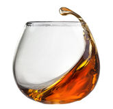 Splash of cognac in glass isolated on white Royalty Free Stock Images