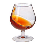Splash of cognac in glass on white background Stock Photography