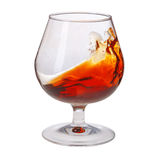 Splash of cognac in glass on white background Royalty Free Stock Photos