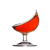 Splash of cognac in glass on white background Royalty Free Stock Photo