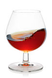 Splash of cognac in snifter glass. Stock Photography