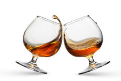 Splash of cognac in two glasses Stock Photography