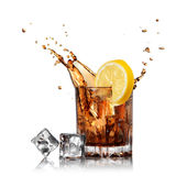 Splash of cola in glass with lemon and ice. Isolated on white Royalty Free Stock Photo