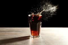 Splash of cola in glass on table Royalty Free Stock Photos