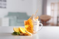 Splash in cup of fresh tea with ginger and lemon on kitchen table stock image