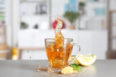 Splash in cup of fresh tea with ginger and lemon on kitchen table stock photography