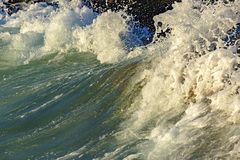 Splash and drops of water. With wave crashing against the stones royalty free stock photography