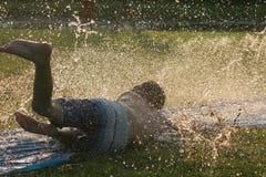 Splash and fun. Boy splashing through water throwing up spray stock images