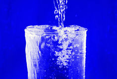 Splash in a glass. Stream  water being poured into a glass. Splash in a glass Stock Image