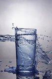 Splash in glass of blue water Stock Images