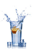 Splash in glass of blue water with orange slice and ice cube Royalty Free Stock Photography