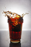 Splash in glass of cola with lemon. On grey gradient background royalty free stock photo