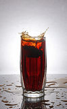 Splash in glass of cola with lemon. On grey gradient background royalty free stock images