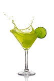 Splash in glass of green alcoholic cocktail drink with lime Royalty Free Stock Photos