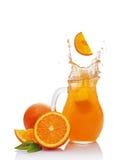 Splash in glass jug of juice with falling slice of orange Stock Images