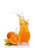 Splash in glass jug of juice with falling slice of orange Stock Photos
