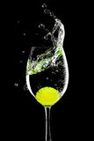 Splash in a glass with lemon ball on a black Royalty Free Stock Photography
