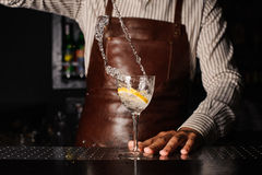 Splash in a glass with lemon barman on background Royalty Free Stock Photography