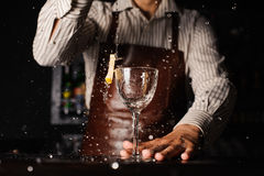 Splash in a glass with lemon barman on background Royalty Free Stock Images