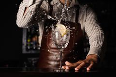 Splash in a glass with lemon barman on background Royalty Free Stock Image