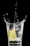 Splash in a glass with lemon and ice on a black Royalty Free Stock Photography