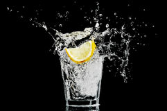 Splash in a glass with lemon and ice on a black ba Stock Photo