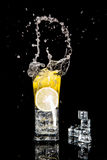 Splash in a glass with lemon and ice Royalty Free Stock Images