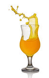 Splash in glass of orange alcoholic tropical cocktail drink Royalty Free Stock Images