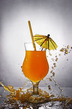 Splash in glass of orange alcoholic tropical cocktail drink with umbrella and straw Stock Image