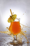 Splash in glass of orange alcoholic tropical cocktail drink with umbrella and straw Stock Photography