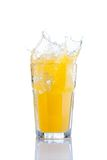 Splash in glass of orange soda with ice cubes Royalty Free Stock Image