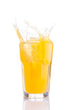 Splash in glass of orange soda with ice cubes. Isolated Stock Photos