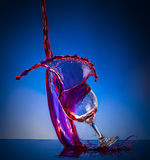 Splash glass red wine. Blue background Stock Photo