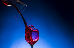 Splash glass red wine. Blue background Royalty Free Stock Images