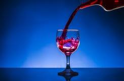 Splash glass red wine. Blue background Stock Photos