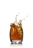 Splash in glass of scotch whiskey with ice cube Stock Image