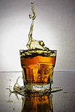 Splash in glass of scotch whiskey with ice Stock Photography
