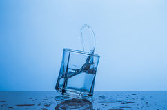 Splash in a glass of water on a blue background Stock Photo