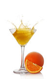 Splash in glass of yellow alcoholic cocktail drink with orange Royalty Free Stock Images