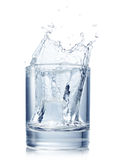 Splash from ice cube in glass of water. Splash from ice cube in a glass of water, isolated on the white background Stock Images