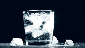 Splash of ice cube in glass water isolated on stock footage