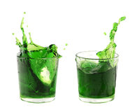 Splash from ice cube in a glasses of green water or drink. Isolated on a white background Royalty Free Stock Images