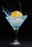 A splash from a lemon in a martini glass. On a black background royalty free stock images