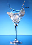 Splash martini on blue Stock Photos