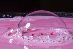 Splash of milk drop in pink color under the buble. Stock Photography