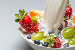 Splash of milk pushes fresh fruit from the bowl Stock Photography