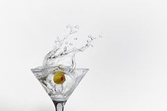 Splash from olive in a glass of cocktail Stock Image
