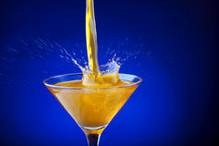 Splash of orange juice on a blue background Stock Images