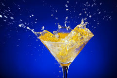 Splash of orange juice on a blue background Stock Photos