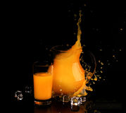 Splash in orange juice in a transparent jug on a black backgroun. D,Juice from fresh oranges stock photo